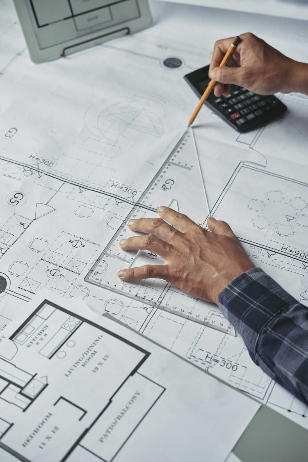 Hands of architect drawing blueprint of the house